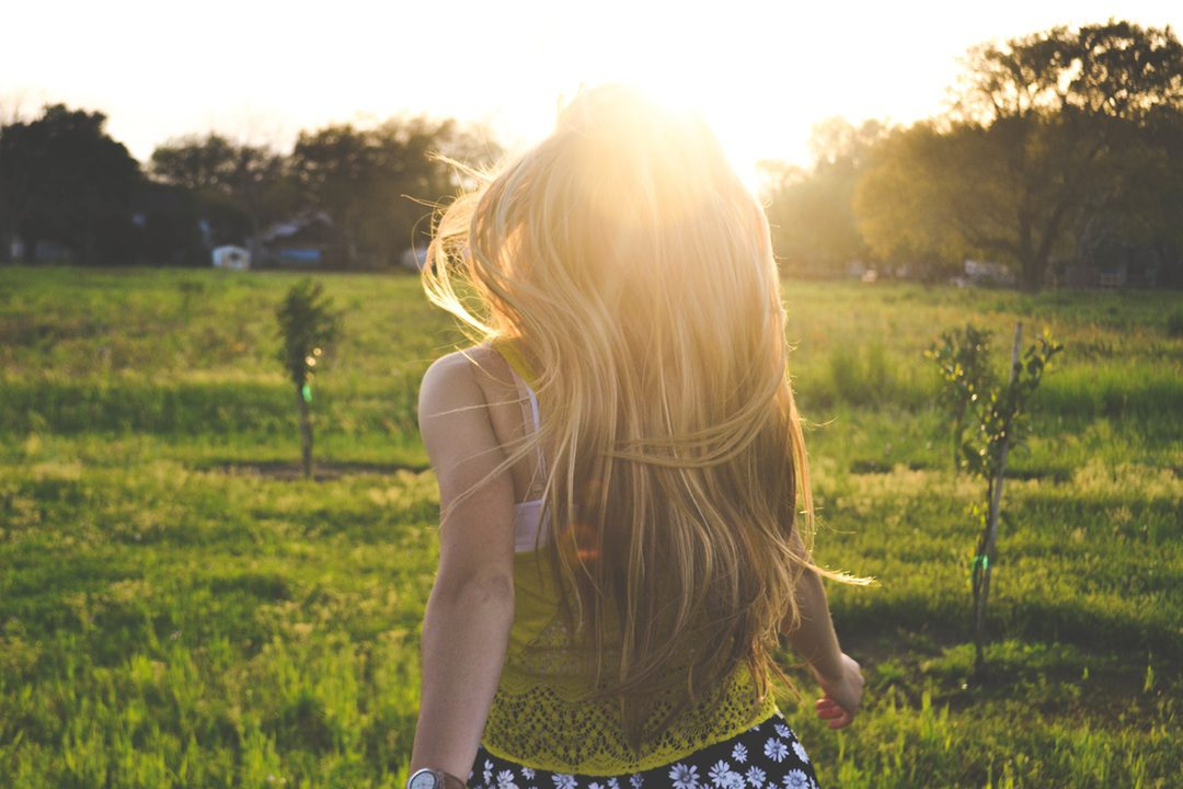 Woman running through a field on a sunny day illustrates the mental affects positivity can have on home care users.